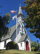 Small white church. Gray roofs. Steeple. Red door. Flagpole