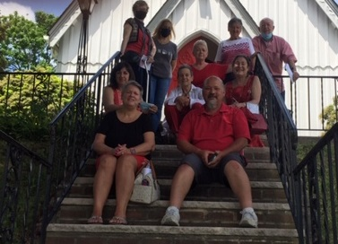 People on steps, wearing red, in front of small white church